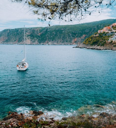 Beautiful blue bay surrounded by mountains in Assos village located on Kefalonia. Summer tourism