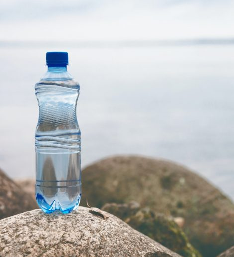 Small water bottle on the ocean stone in natural background